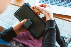 A credit card pulled out of a wallet over a laptop